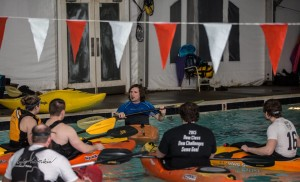 Hanley Loller, pictured center, speaks before demonstrating a kayak roll. Kayakers of all levels gathered to learn and practice rolls at the Pinnacle Pool in Lexington on Friday night.  The Bluegrass Wildwater Association hosts a series of winter pool sessions for kayakers to learn and perfect this essential whitewater technique. (Photo courtesy of Kyle Koeberlin, Photo Landmark).