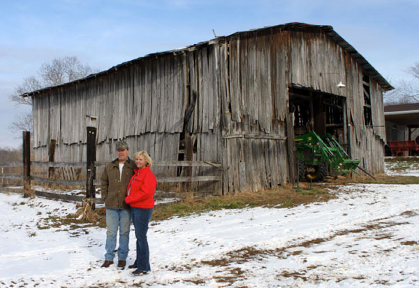 Terry and Lisa Osborne in front of their converted 1950s tobacco barn. The barn on their farm in Load is used now for a tractor and hay barn.